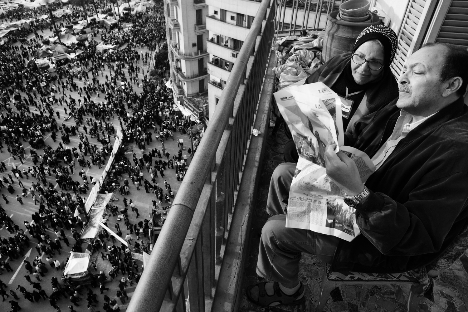 A senior couple reads an Egyptian newspaper overseeing the protests against Egyptian dictator Hosni Mubarak on Tahrir square.