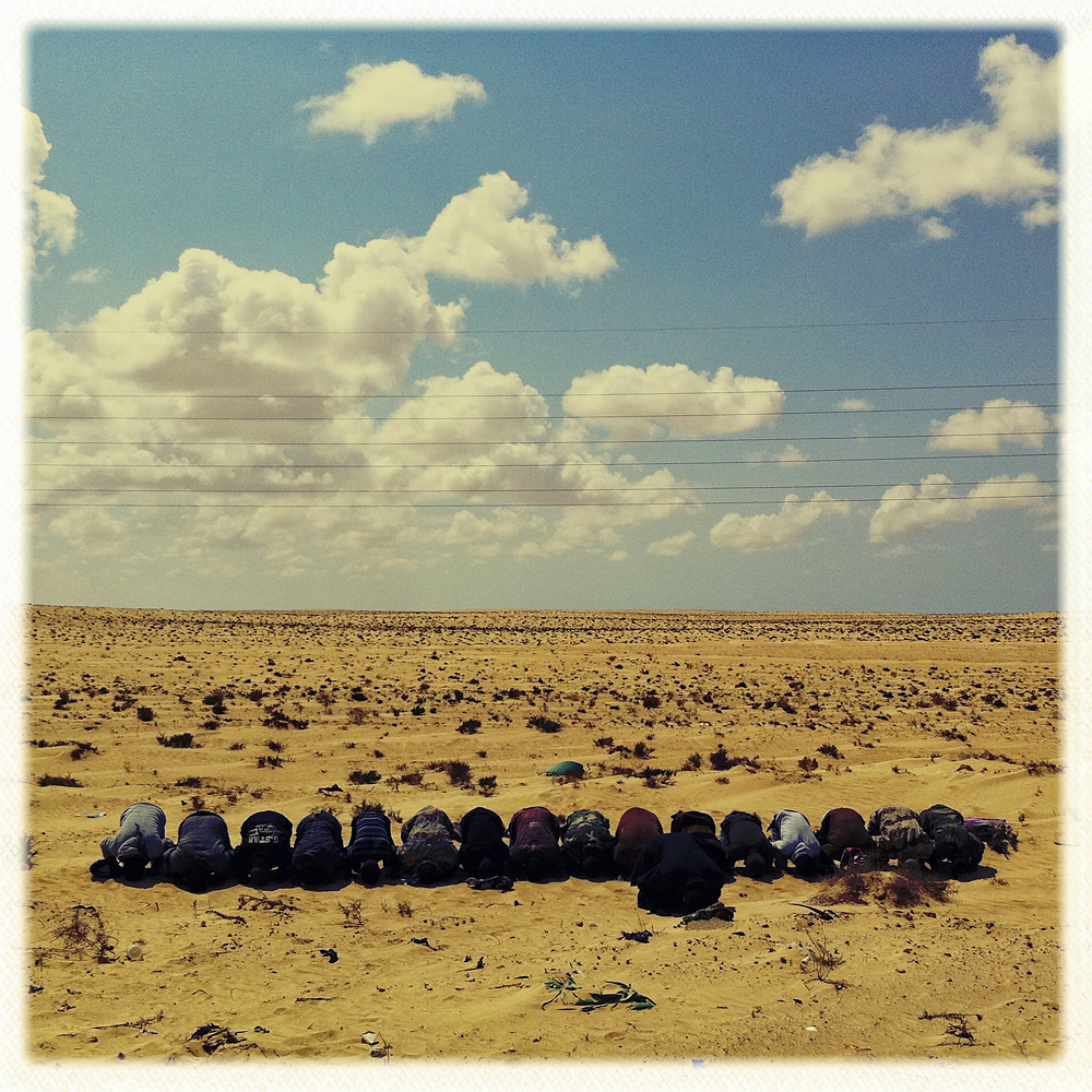 Opposition fighters pray on the front line, Ajdabiya, Libya, March 22, 2011.