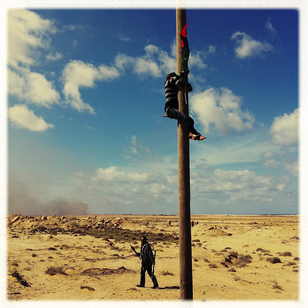 Opposition fighter hanging the flag of the Libyan Republic, Bin Jawad, Libya, March 6, 2011.