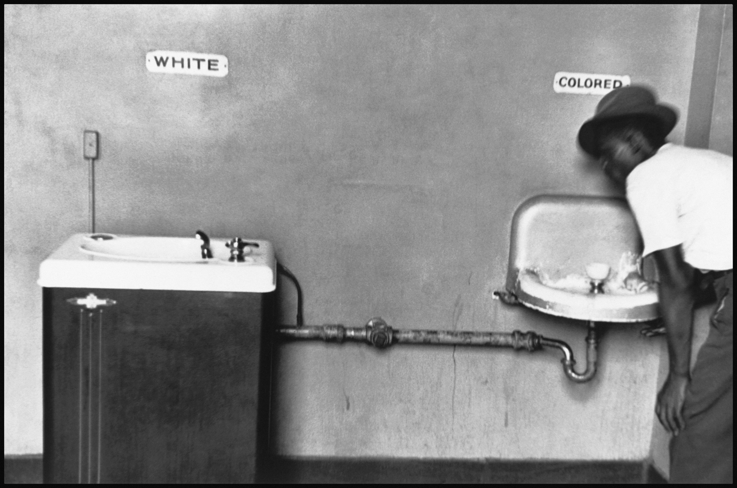 "North Carolina, 1950. ""This is probably one of my better pictures. The ""White"" and ""Colored"" drinking fountain united by one pipe, but a refrigerated one for ""White"" people and one messy, ugly, dirty one for ""Colored"" people. This was taken in North Carolina in the 1950's. It's a picture that's been used quite a lot in history books as an illustration to show graphically the myth of separate but equal, which was the mantra of the time in the South. """