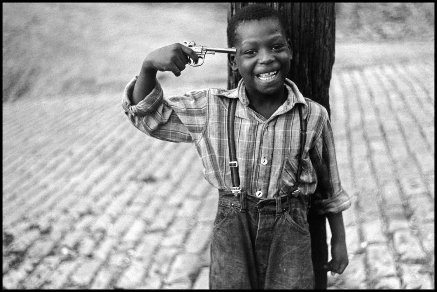 "Pittsburgh, Pennsylvania, 1950. ""This is another favorite early photo of mine taken in Pittsburgh in 1950. Its shows a black boy with a gun to his head. Again, it's a picture, but you can make out of it whatever you wish. I was there working for Roy Stryker, documenting Pittsburgh as it was about to experience big change. The entire point of Pittsburgh was being demolished for new buildings and Roy (who worked for the FSA) hired me, along with a lot of other photographers, to document it."""