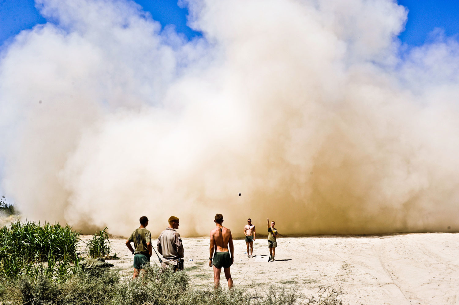 U.S. Marines play a game that tries to get beanbags in a hole as a helicopter lands in the background in a cloud of dust. Helmand Province, Iraq, 2008.