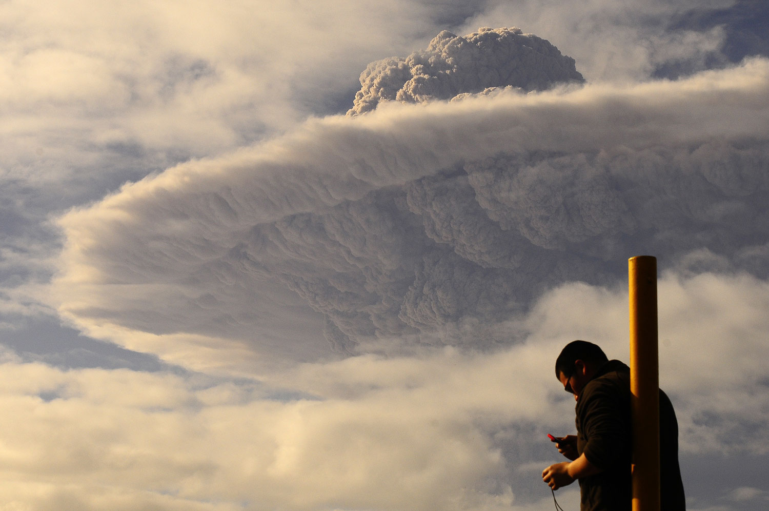 A tourist watches the cloud of ash billowing from Puyehue volcano at a town in southern Chile, June 5, 2011.