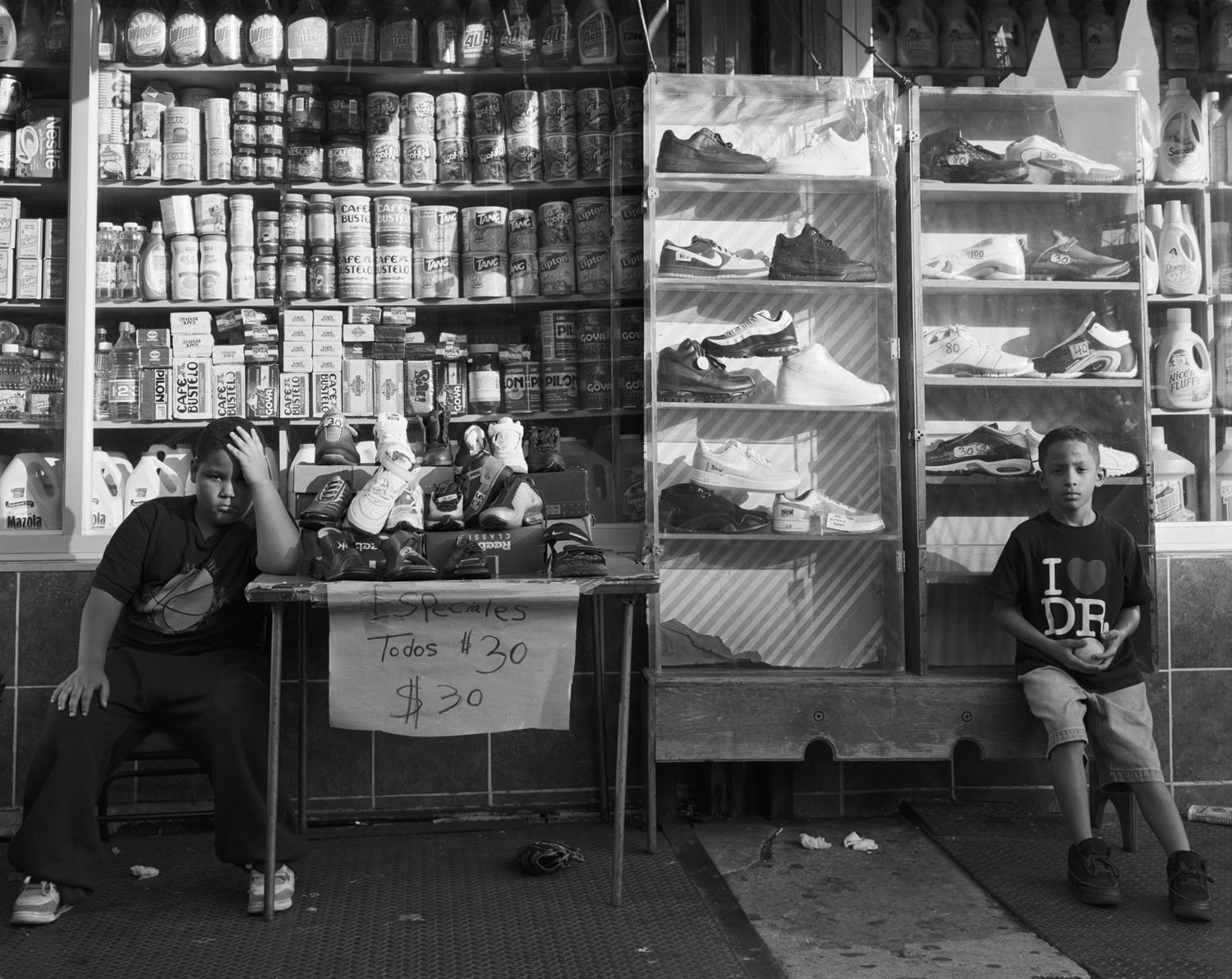 Two young men sit outside a store on Broadway, in northern Manhattan. 2007.