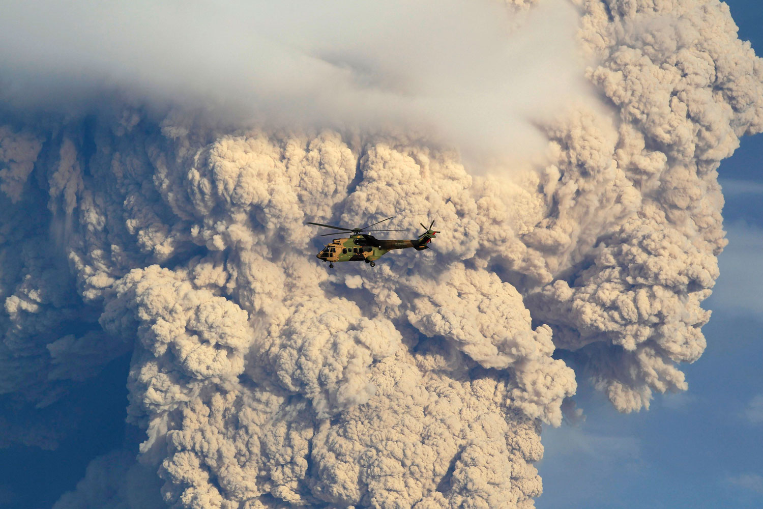 A helicopter flies over smoke and ash rising from the Puyehue-Cordon Caulle volcanic chain near Osorno city in south-central Chile June 5, 2011.