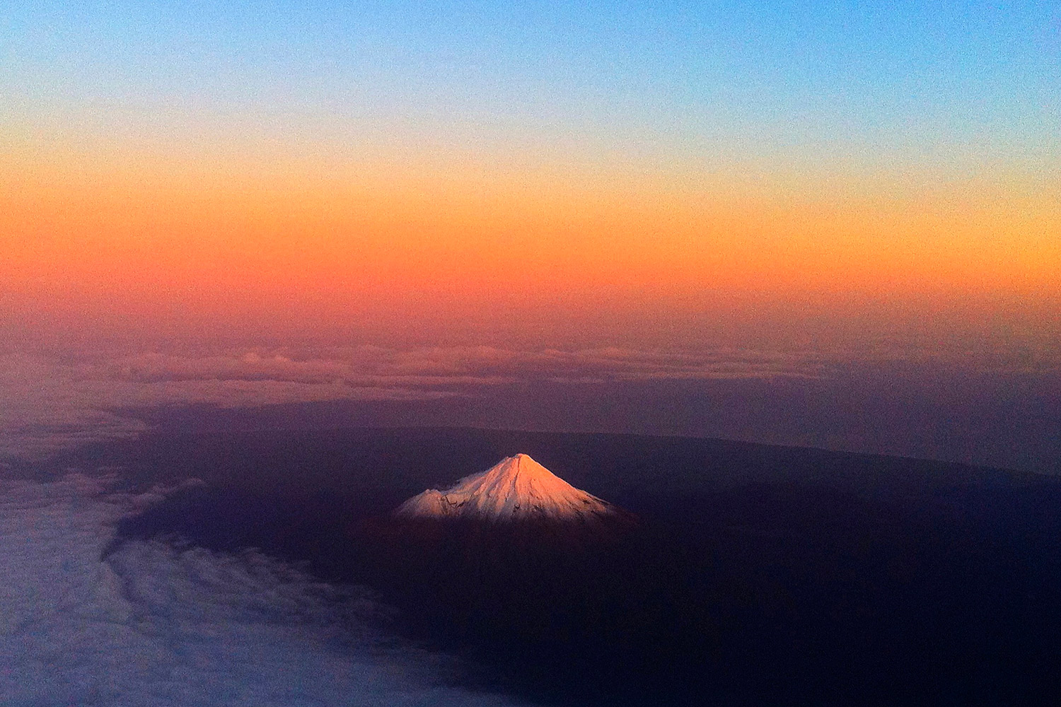 The ash cloud from the Chilean volcano has drifted across the Pacific, giving New Zealand's Mount Taranaki, above, a warm glow, June 12, 2011.