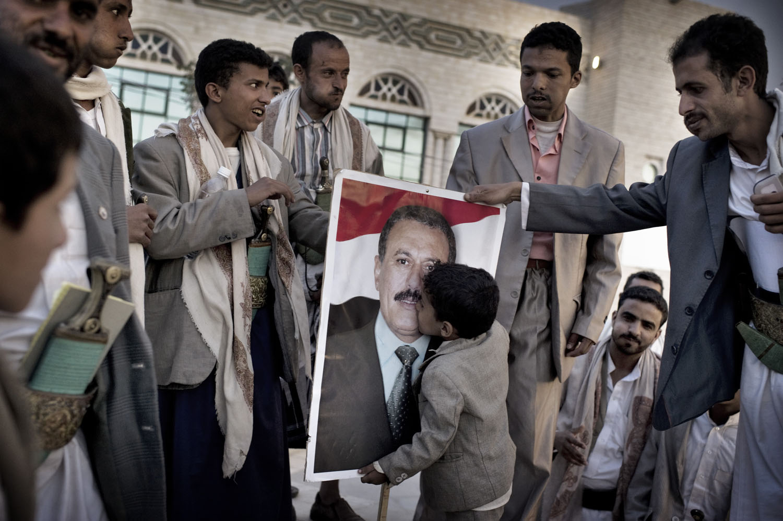 A boy kisses a poster of Yemen's President Ali Abdullah Saleh, May 17, 2011.