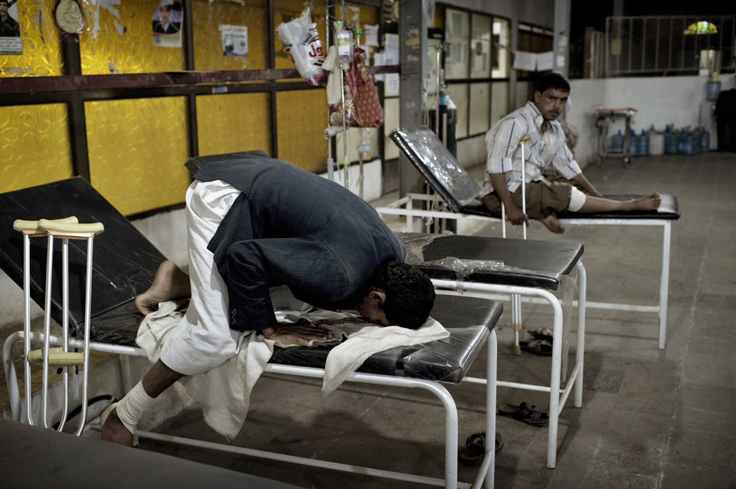 A wounded Yemeni anti-government protester prays at a makeshift field hospital in Sana'a, May 19, 2011.