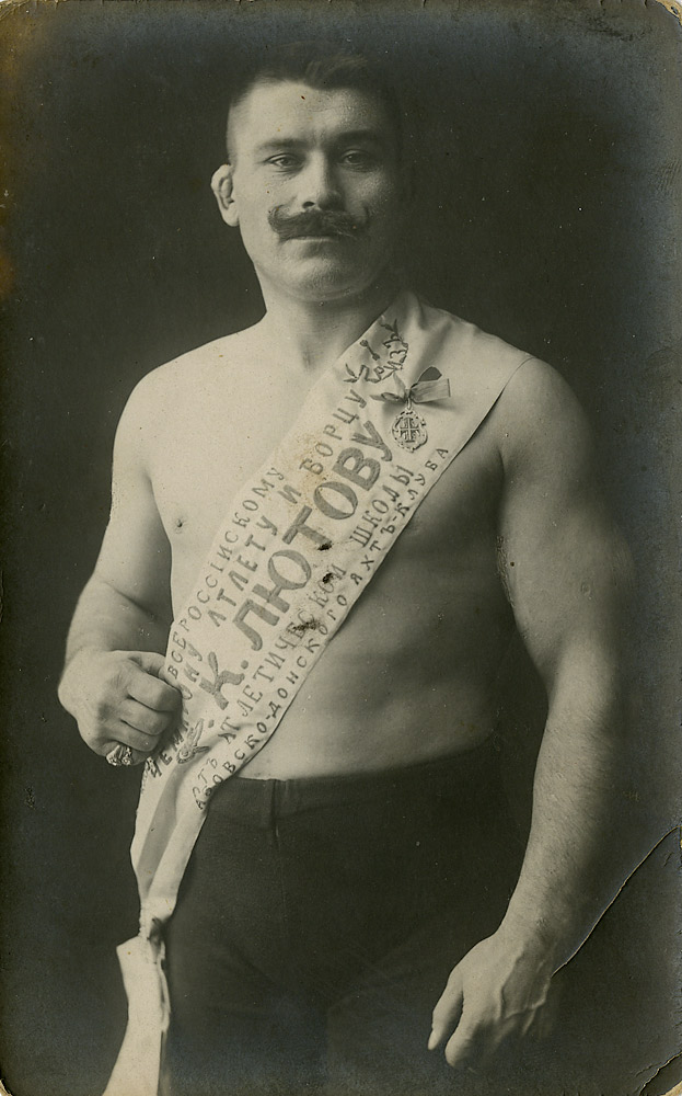 Liutov, a photo postcard; his sash declares him to be the champion of Russia