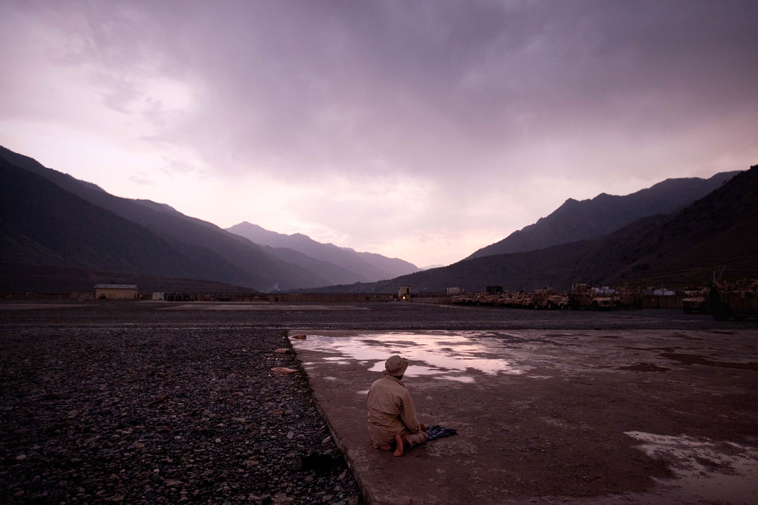 July 3, 2011. An Afghan man prays at sunset on a helipad following a rainstorm at Forward Operating Base Bostick in Kunar province, Afghanistan.
