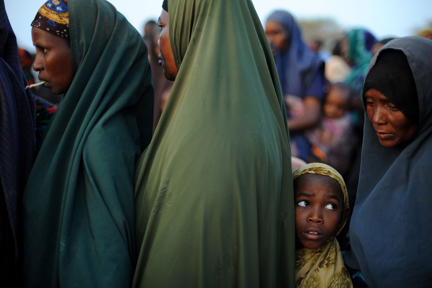 July 5, 2011. A young Somali girl who fled violence and drought in Somalia stands in line among adults outside a food distribution point in Dadaab refugee camp in northeastern Kenya. Dadaab, a complex of three settlements, is the world's largest refugee camp. Built to house 90,000 people and home to more than four times that number, it was already well over its maximum capacity before an influx of 30,000 refugees in the month of June.