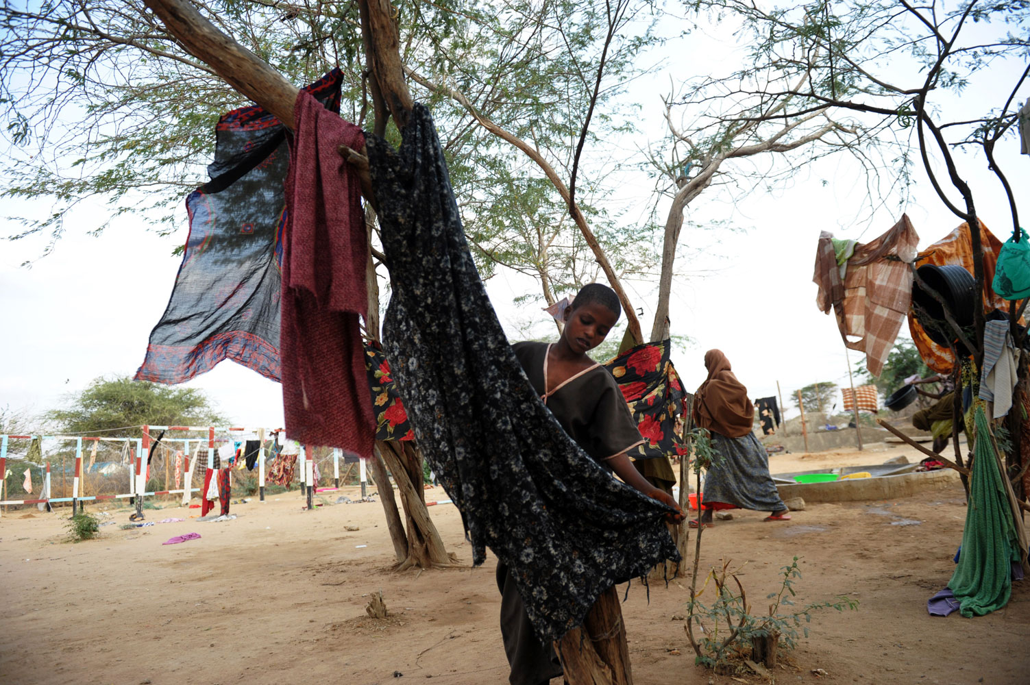 July 5, 2011. Seven-year-old Fartun Hassan hangs a cloth she had just washed on a tree at a Medecins Sans Frontieres (Doctors Without Borders) hospital at the Dadaab refugee camp in northeastern Kenya.