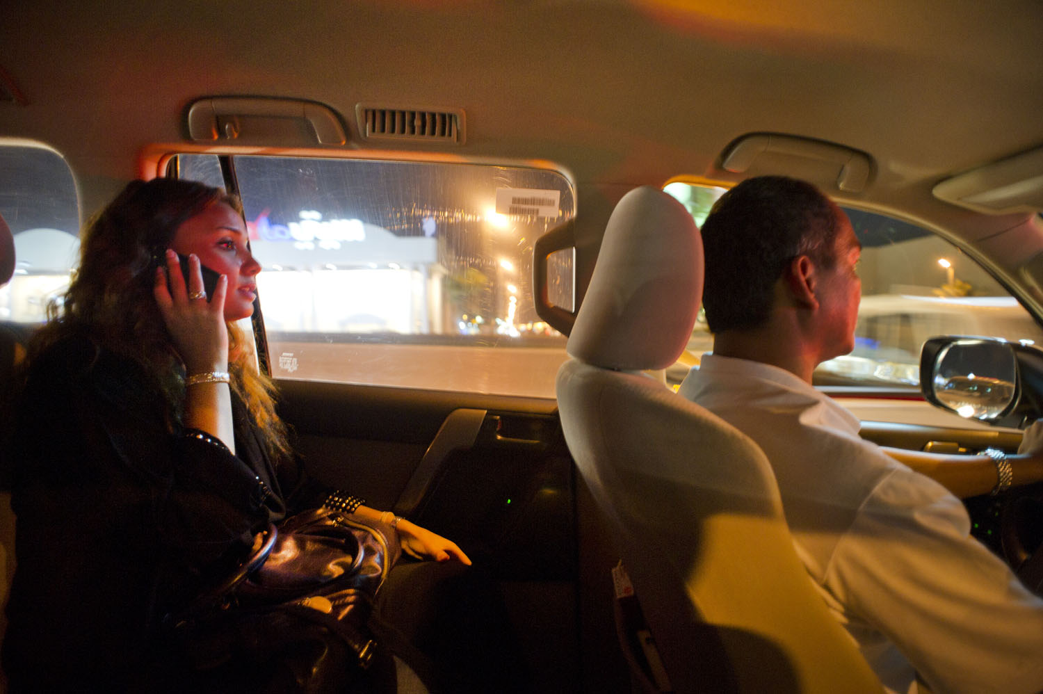 A Saudi woman talks on the phone as she is driven by a driver out for the evening in Jeddah, Saudi Arabia, June 16, 2011. On June 17, a group of Saudi women have called for a nation-wide challenge to the ban on women drivers across the country.