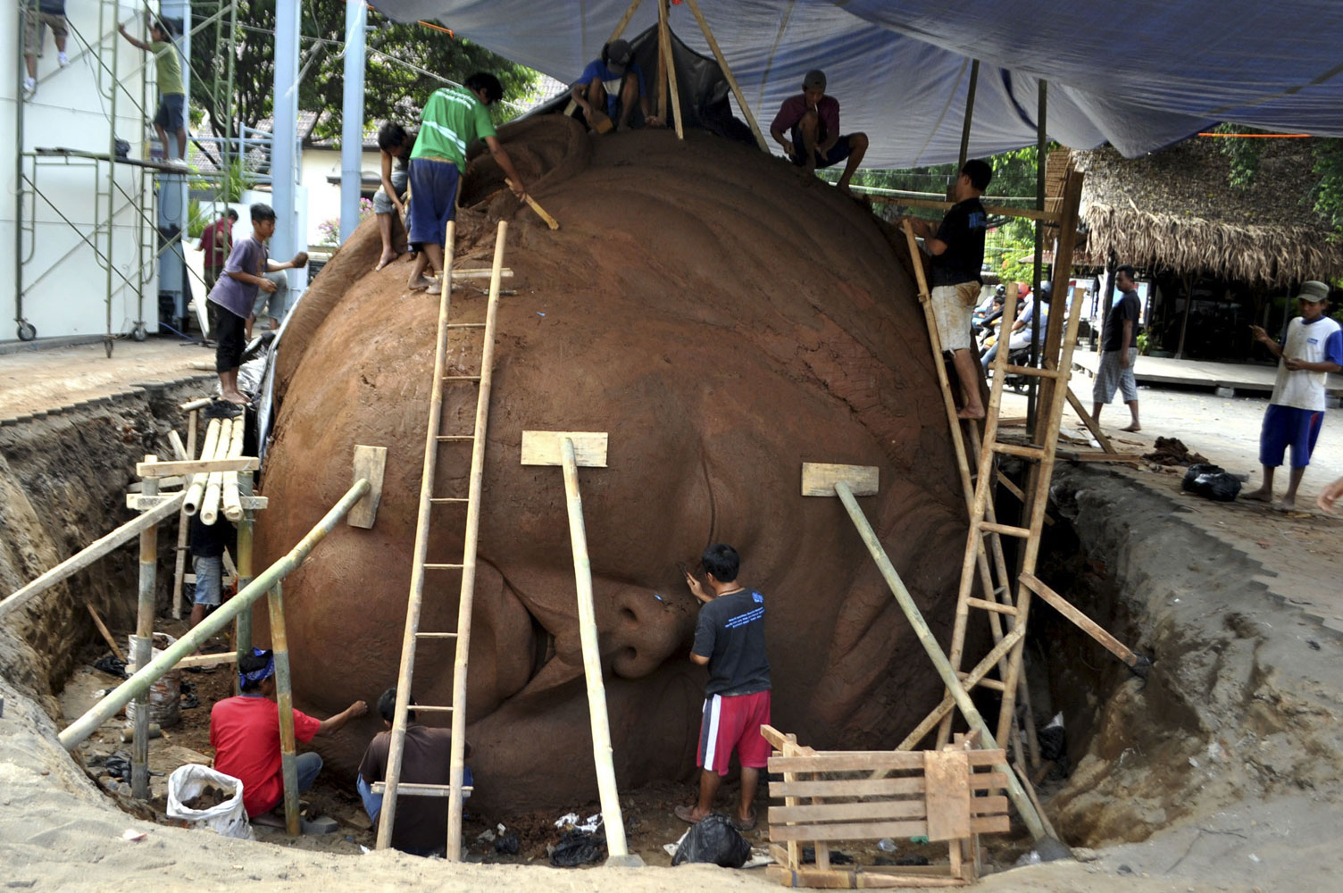 July 7, 2011. Indonesian artists make a sculpture of a child from clay in preparation for Yogyakarta art festival in Yogyakarta, Central Java, Indonesia.