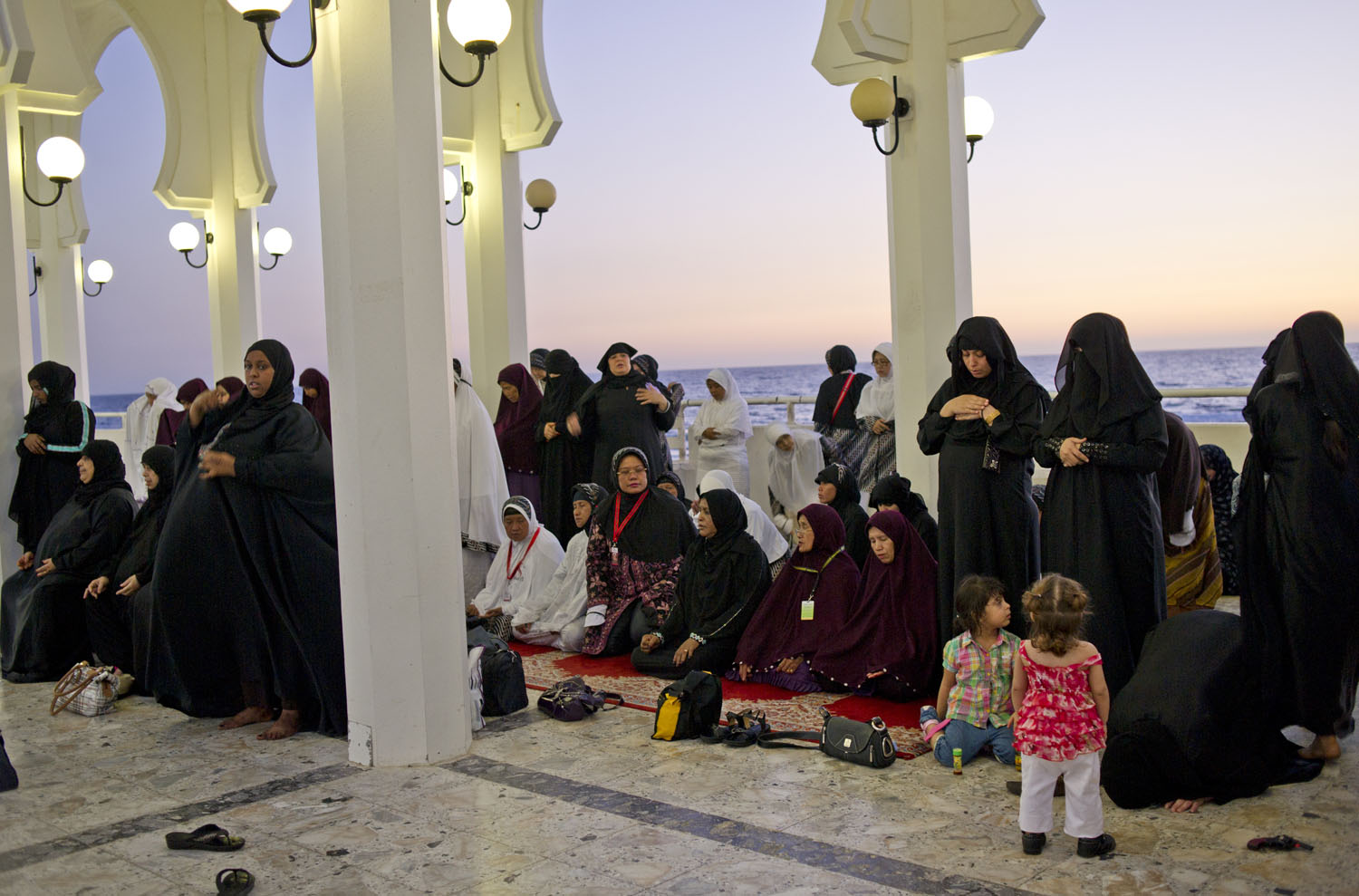 Saudi women pray alongside a group of Indonesian tourists along the corniche in Jeddah, Saudi Arabia, June 14, 2011.  Saudi Arabia is governed by Sharia Law, rule according to Islam, and religion is ever present in society across the country.