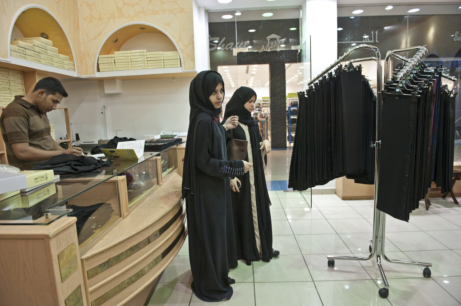 Saudi cousins Bayan, 20, and Seba, 19, shop for a new abaya for Seba in the Sahara mall in Riyadh, Saudi Arabia, June 11, 2011. There are few social spaces for singles and families to gather in Riyadh outside of malls, and many families and young people spend evenings lingering at one of dozens of malls around the city.