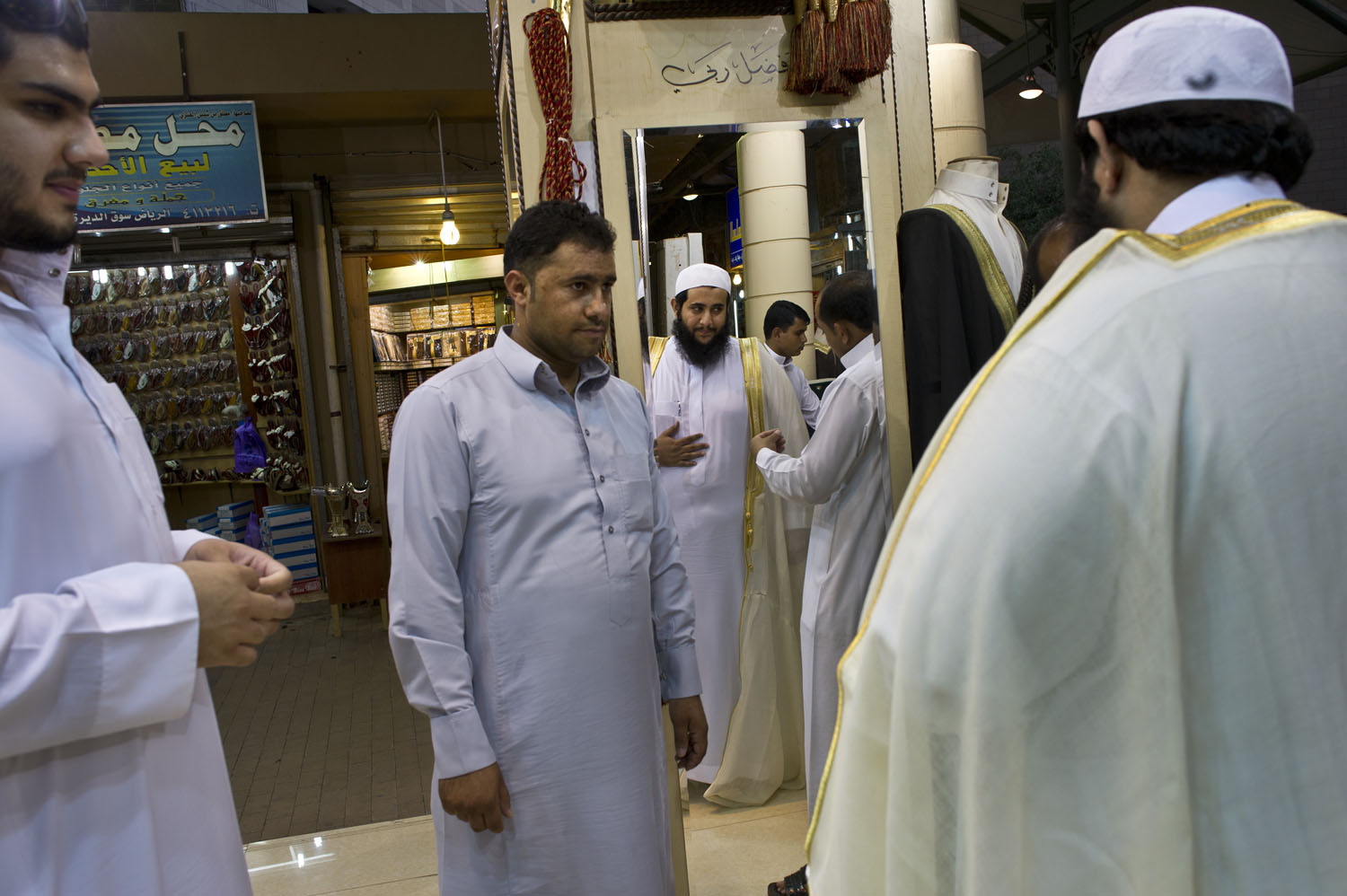 28-year-old IT consultant Ali el Saddou tries on a Bisht, a finely woven traditional robe (the Saudi equivalent of a tuxedo), which he will wear for his wedding in two weeks, as his brother, Mana, 21, far left, looks on, in Riyadh's old bazaar, in Riyadh, Saudi Arabia, June 10, 2011. Ali al Saddou will marry his cousin in a traditional arranged marriage in the Kingdom's capital, a tradition that is very common in the Kingdom.