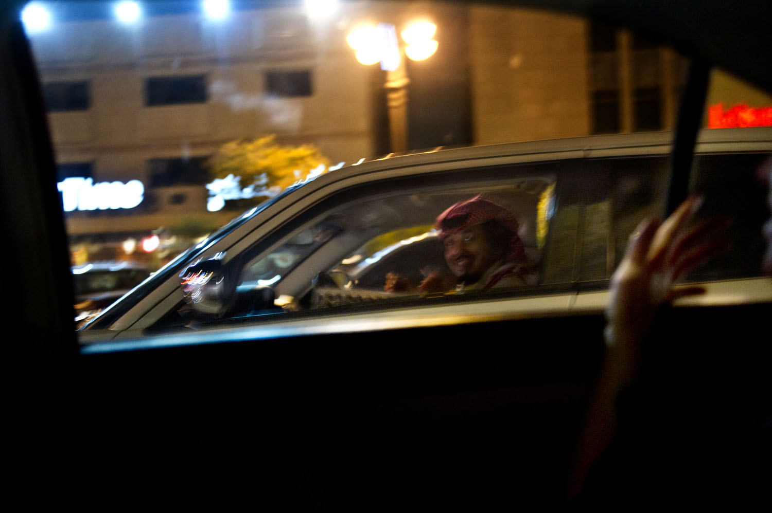 Young Saudi men hold up their phone numbers on a Thursday night in traffic as they try to pick up women in Riyadh, Saudi Arabia, June 9, 2011.  Because of social and societal restrictions, young men and women cannot flirt and socialize openly, so young people are constantly devising ways to interact with women. Reciting their phone numbers aloud, holding them up in public, and etching blackberry pin numbers onto cars are just a few ways young men try to get women to call them.