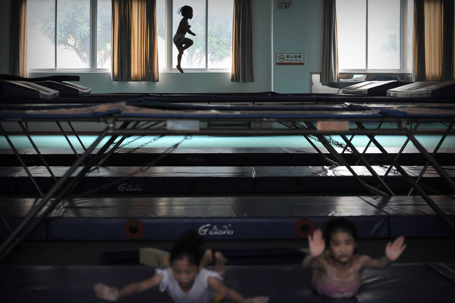 July 6, 2011. Children on the provincial children's gymnastics trampoline team exercise in a gym in Fuzhou in southeast China's Fujian province. Over 30 children under age 12 in the team, selected from around the province, go through hard training in the sports center, aiming to be Olympic medalists in the future.