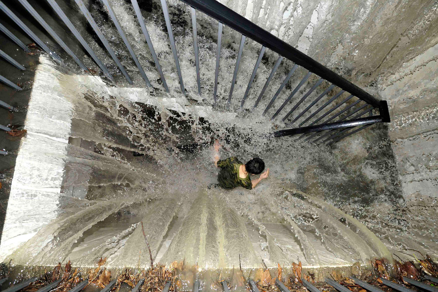 July 3, 2011. A resident runs on a flooded stairway as floodwater pours into an underground garage amid heavy rainfalls in Chengdu, Sichuan province. Heavy downpours hit Chengdu on Sunday, flooding roads and breaking down city traffic.