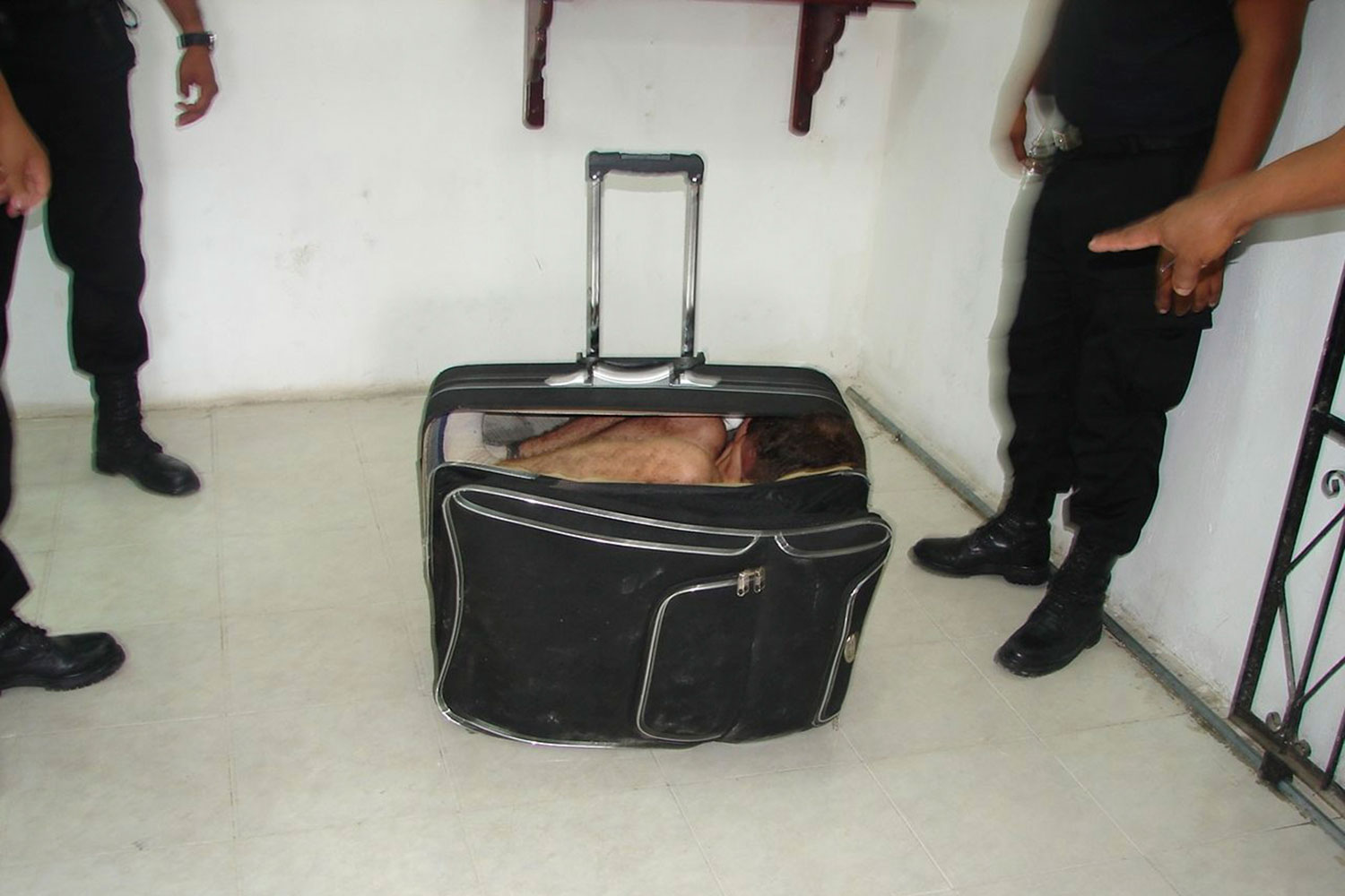 July 2, 2011. Prison guards stand around inmate Juan Ramirez Tijerina as he hides in a suitcase during an escape attempt from a prison in Chetumal in this July 2, 2011 handout photo. Ramirez Tijerina tried to escape from prison by hiding inside the suitcase after a conjugal visit on Saturday, according to the authorities.