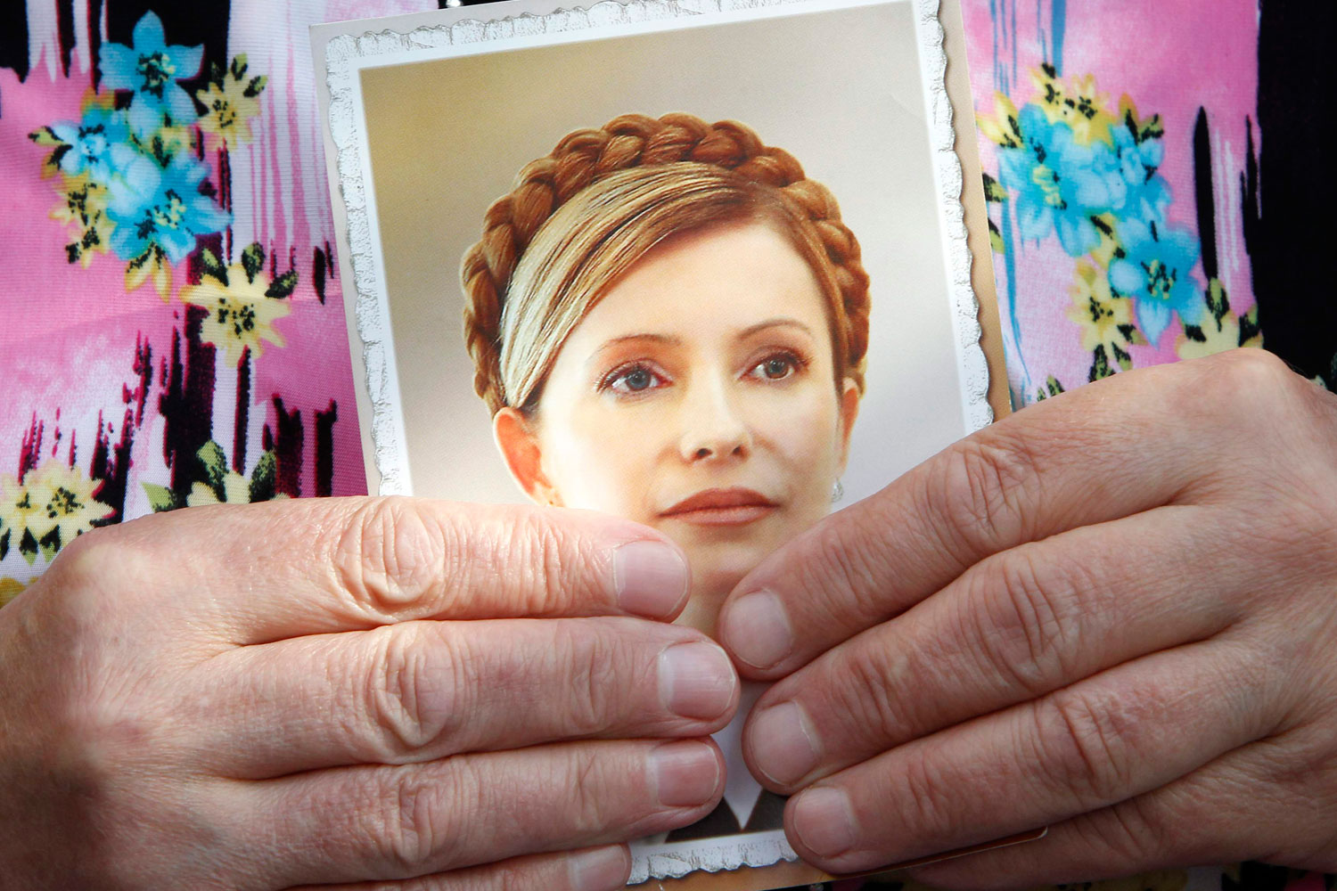 July 6, 2011. A supporter holds a portrait of Ukraine's former Prime Minister Yulia Tymoshenko during a session outside a court building in Kiev July 6, 2011.