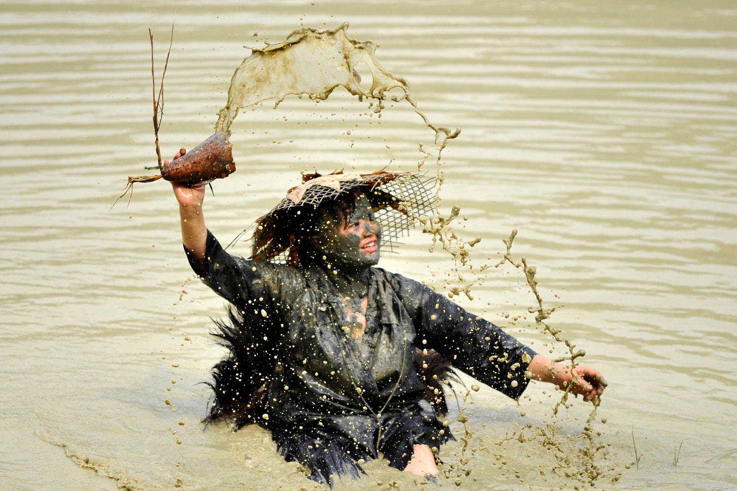 July 6, 2011. A woman splashes water with a container as she performs the Shuigu dance during a cultural festival in Jianhe county, Guizhou province. The dance, which is also known as the water drum dance, has a history of over 500 years in local Miao villages.