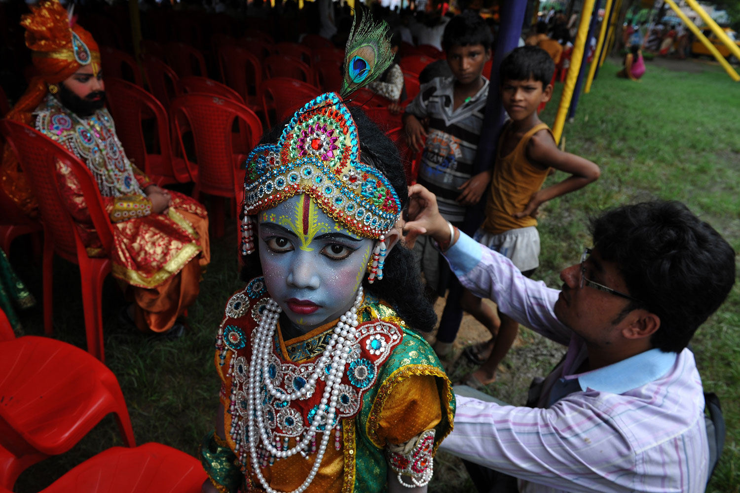 July 3, 2011. A young Indian Hindu devotee looks at the camera while being dressed as Lord Krishna as she waits to participate in the  Rath Yatra , along with Sri Krishna devotees from the International Society for Krishna Consciousness (ISKCON), in Kolkata. According to mythology, the Rath Yatra dates back some 5,000 years when Hindu God Krishna along with his older brother Balaram and sister Subhadra were pulled on a chariot from Kurukshetra to Vrindavana by Krishna's devotees.
