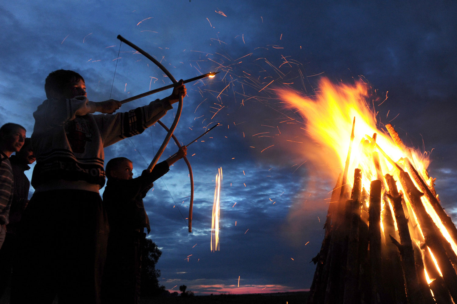 July 7, 2011. Boys shoot flaming arrows during celebrations for Ivan Kupala, the feast of St John the Baptist, a traditional Slavic orthodox holiday celebrating the summer solstice, 270 kilometers south from Minsk in Turov.