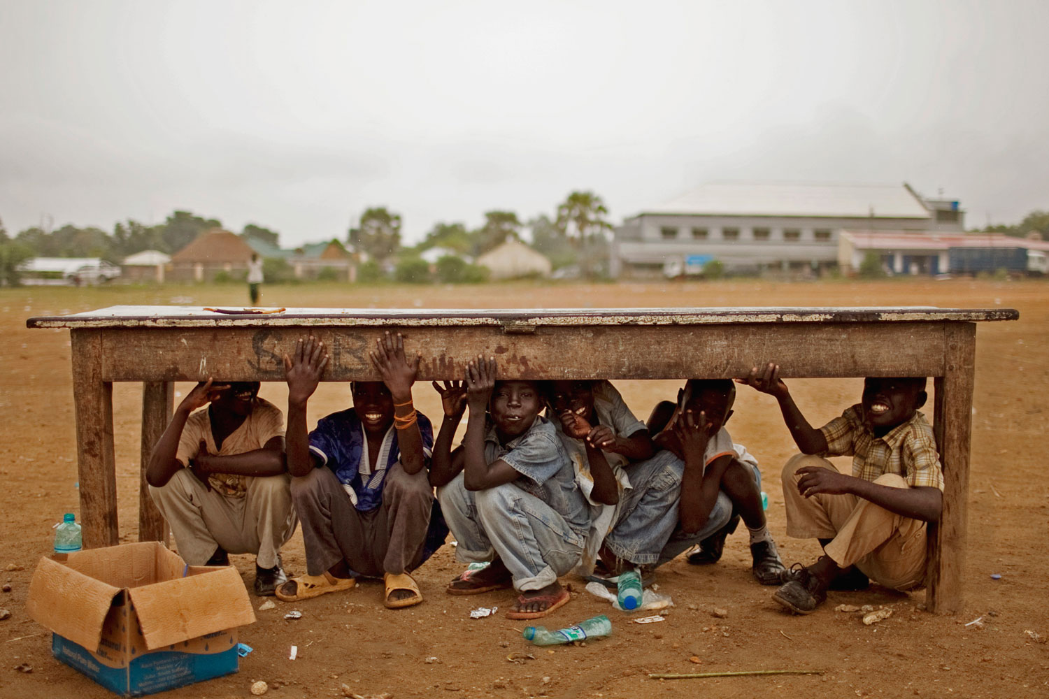 July 4, 2011. Southern Sudanese boys take shelter from afternoon rains that disrupted rehearsals for independence day celebrations in the capital city of Juba. Southern Sudan is set to declare independence from the north on July 9.