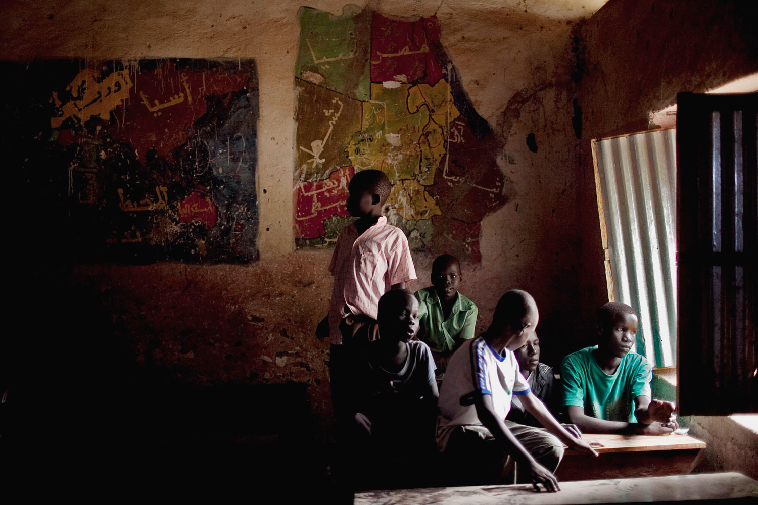 July 4, 2011. Southern Sudanese boys take shelter from afternoon rains that disrupted rehearsal for independence day celebrations in the capital city of Juba. The mural behind the boys depicts a map of the united Sudan.