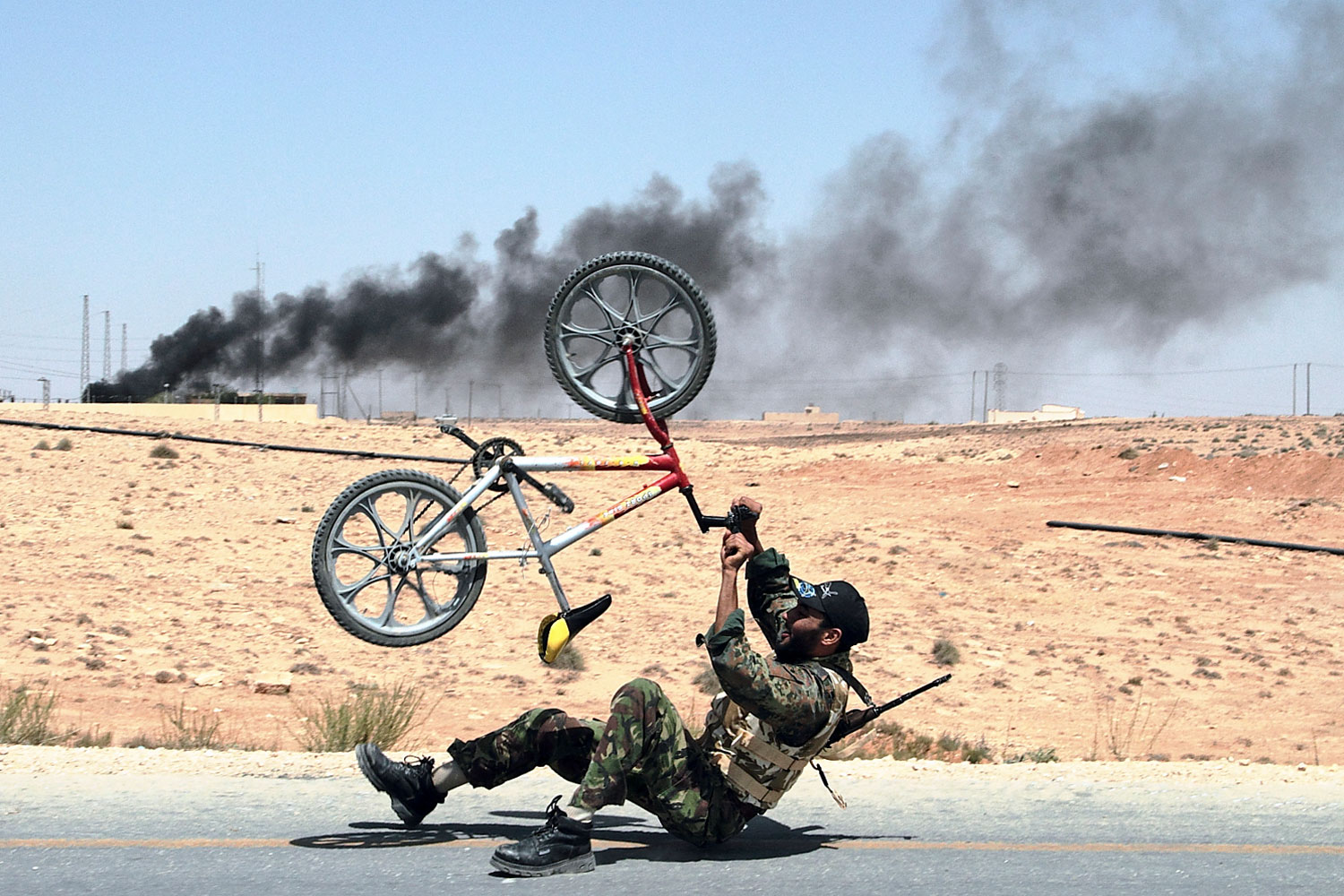 July 6, 2011. A rebel with a bicycle celebrates the liberation of al-Qawalish, 100 kilometers (60 miles) southwest of Tripoli, Libya, after six hours of battle. In the background smoke rises from a the power station that was shelled by retreating soldiers loyal to Moammar Gadhafi.