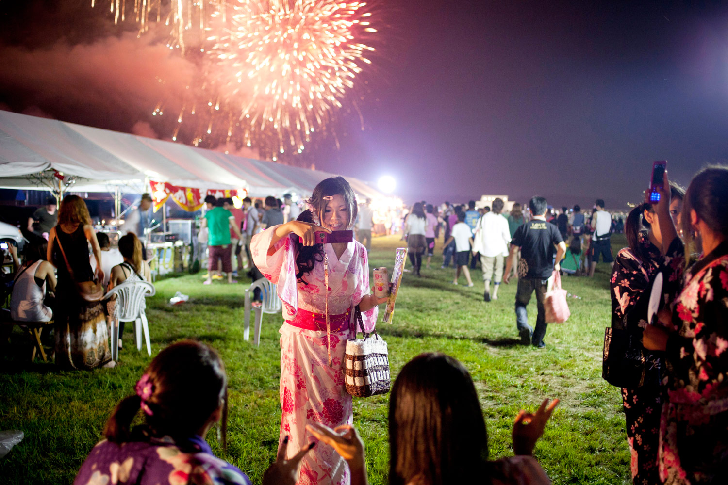 Girls photograph each other during the memorial fireworks display in Soma, August 13, 2011.