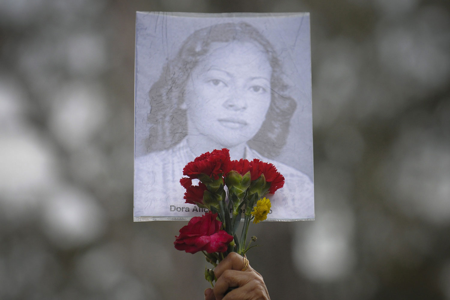 July 30, 2011. A victim's photograph is held up during a rally to commemorate the 36th anniversary of a massacre of student protesters carried out by soldiers in San Salvador in 1975. San Salvador, El Salvador.  Demonstrators asked Salvadoran President Mauricio Funes to create a special commision to investigate the massacre.