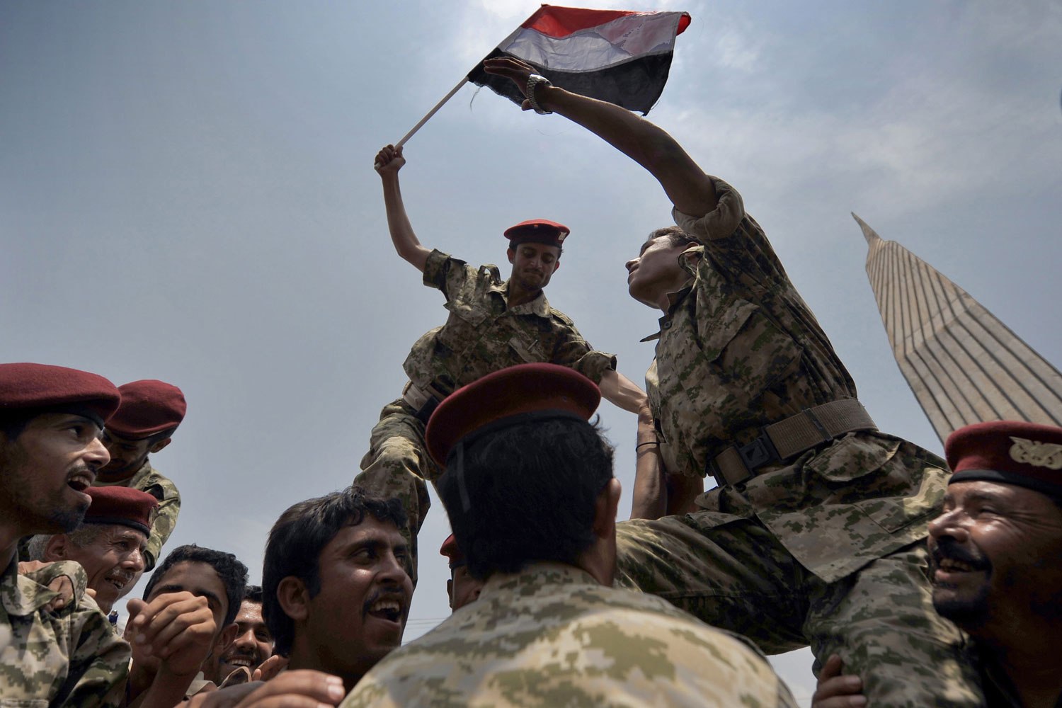 July 31, 2011. Yemeni soldiers hold up a Yemeni flag as they join anti-government protesters during a protest against the 33-year regime of  President Ali Abdullah Saleh, in Sana'a, Yemen.