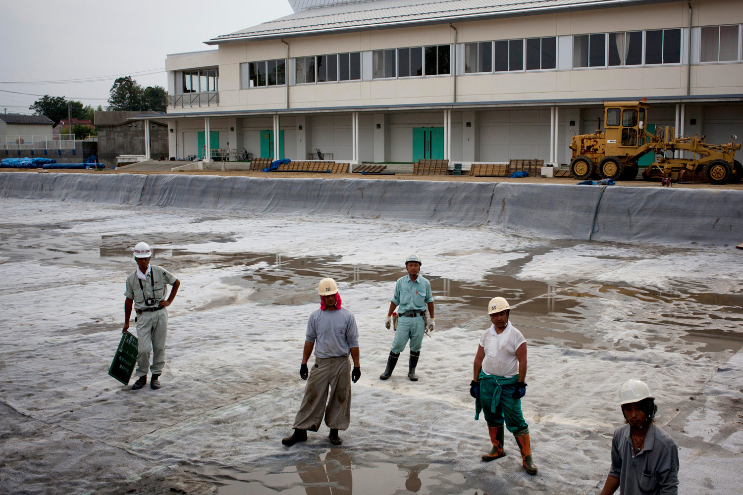 Workers prepare a huge hole near a public school in Minamisoma that will be used to bury contaminated soil August 12, 2011. The contaminated soil is covered with a minimum of 20 inches of clean topsoil, a process that officials say has lowered ground radiation levels by 80%.