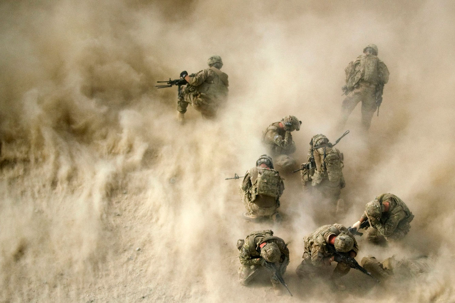 August23, 2011. U.S. troops in Afghanistan gather near a destroyed vehicle, protecting their faces from rotor wash as a medevac helicopter airlifts their wounded comrades. Three soldiers were hurt when their vehicle was destroyed by an improvised explosivedevice.