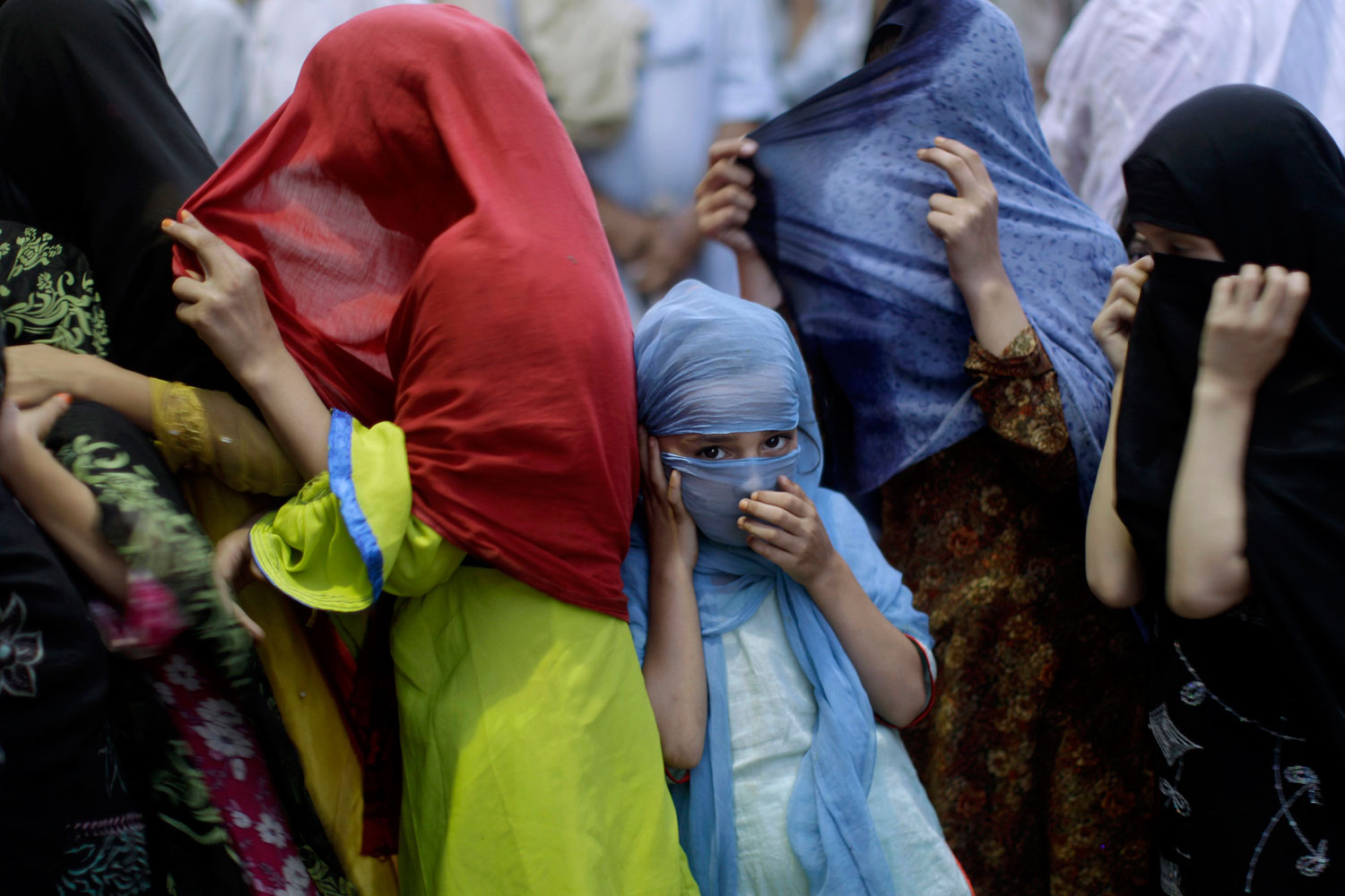 August19, 2011. A Pakistani girl in Rawalpindi lines up with other women to receive a donated meal during the month of Ramadan. The food is paid for by wealthy local Muslims who give money to feed the poor during Islam's holiest month.