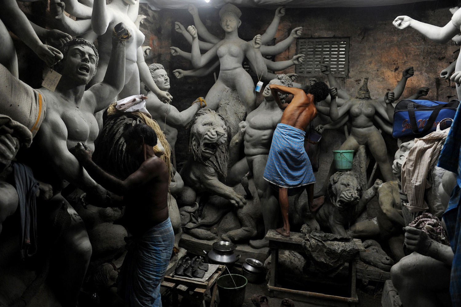 August 22, 2011. Artisans work on semi-finished clay statues of the Hindu goddess Durga in Kumartuli, a neighborhood of Kolkata famed for its clay idols. Ongoing monsoon rains have made it hard for idolmakers to finish onschedule.