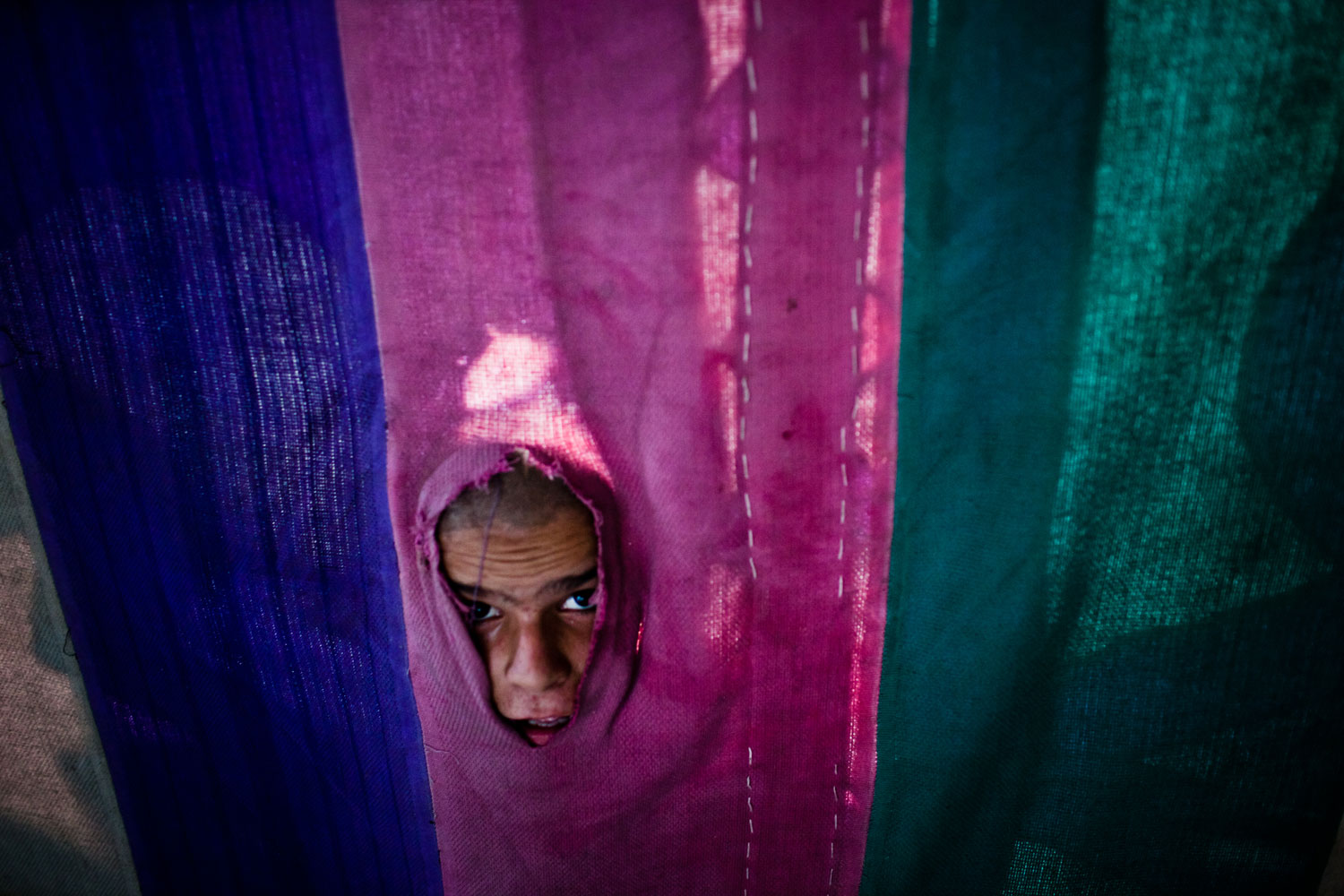 August 3, 2011. A boy peers through a food tent whilst awaiting a handout meal before 'Iftar', when Muslims break their fast, during the holy month of Ramadan on in Islamabad, Pakistan.