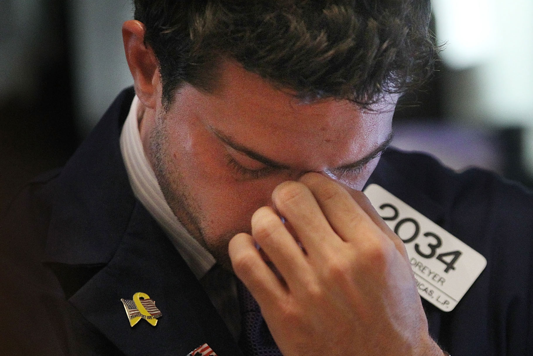 NEW YORK, NY - AUGUST 04:  A trader bows his head on the floor of the New York Stock Exchange after the closing bell on August 4, 2011 in New York City. The Dow plunged more than 500 points and is down more than 1,200 points since July 21. It was the market's worst one-day drop in more than two years.