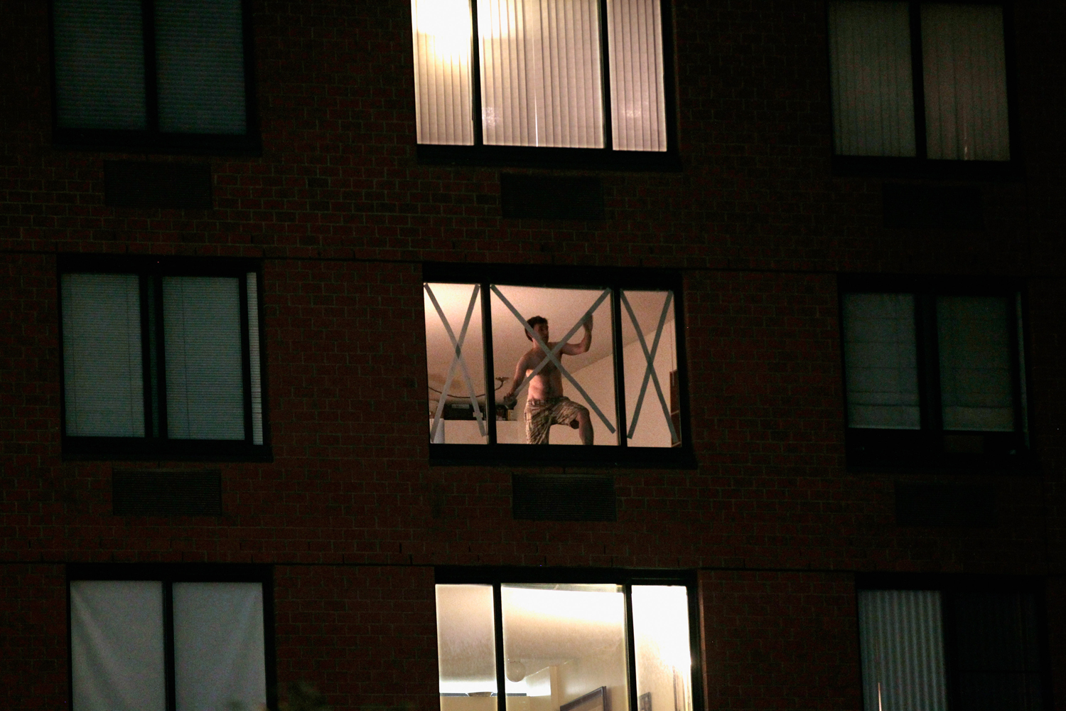 August 26, 2011, New York, NY.  A man in a Battery Park City high rise tapes his windows ahead of the arrival of Hurricane Irene. New York City Mayor Michael Bloomberg had ordered a mandatory evacuation of 250,000 residents of low-lying areas at the city's edges, including the World Financial Center.