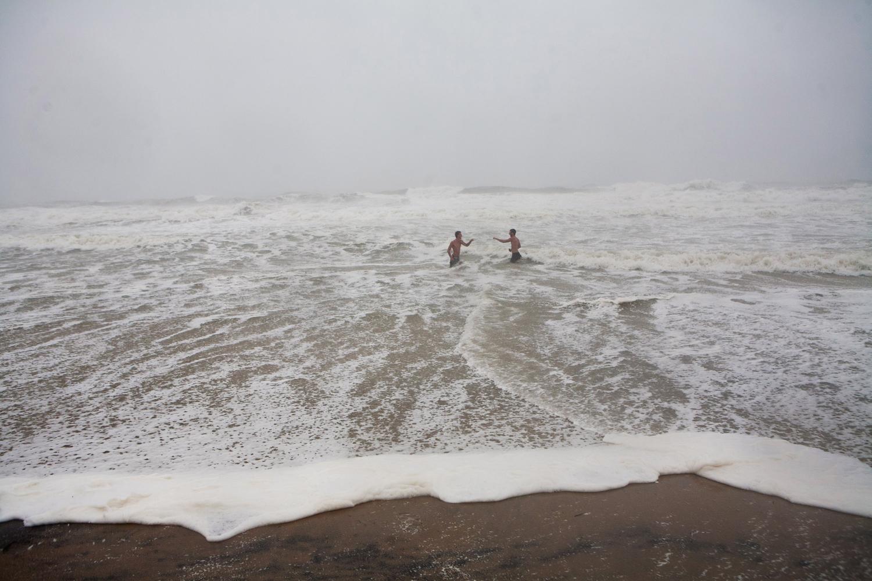 August 27, 2011 in Virginia Beach, Va. Crae Kalista, left, and Joseph Lacy, of Virginia Beach, take a brief swim in the high surf in advance of Hurricane Irene.