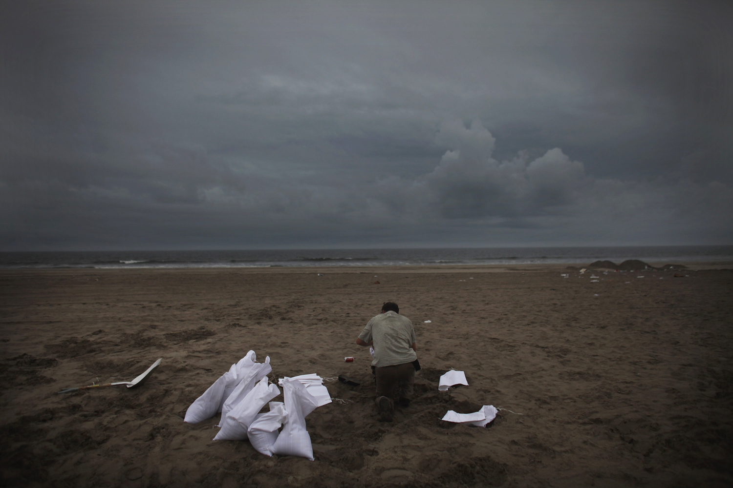 August 27, 2011, New York, NY. A man fills sand bags at 128th St. beach in the Rockaways in preparation for Hurricane Irene.