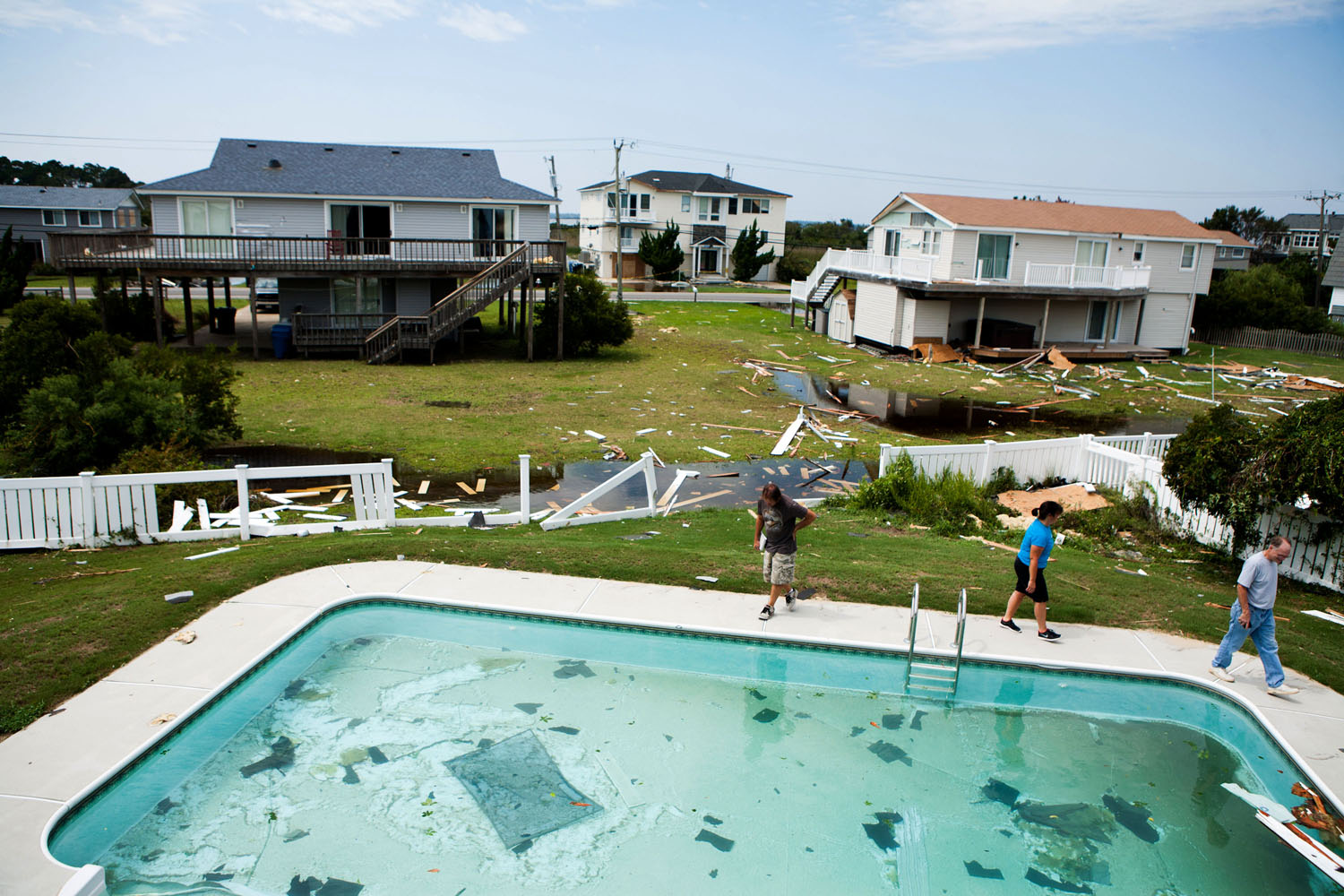 August 28, 2011, Virginia Beach, VA. Shane Argabright, left, a general contractor, surveys damage to a house belonging to Aileen Black, center, and Reed Black in Sandbridge the day after a tornado spawned by Hurricane Irene passed through the town in Virginia Beach.