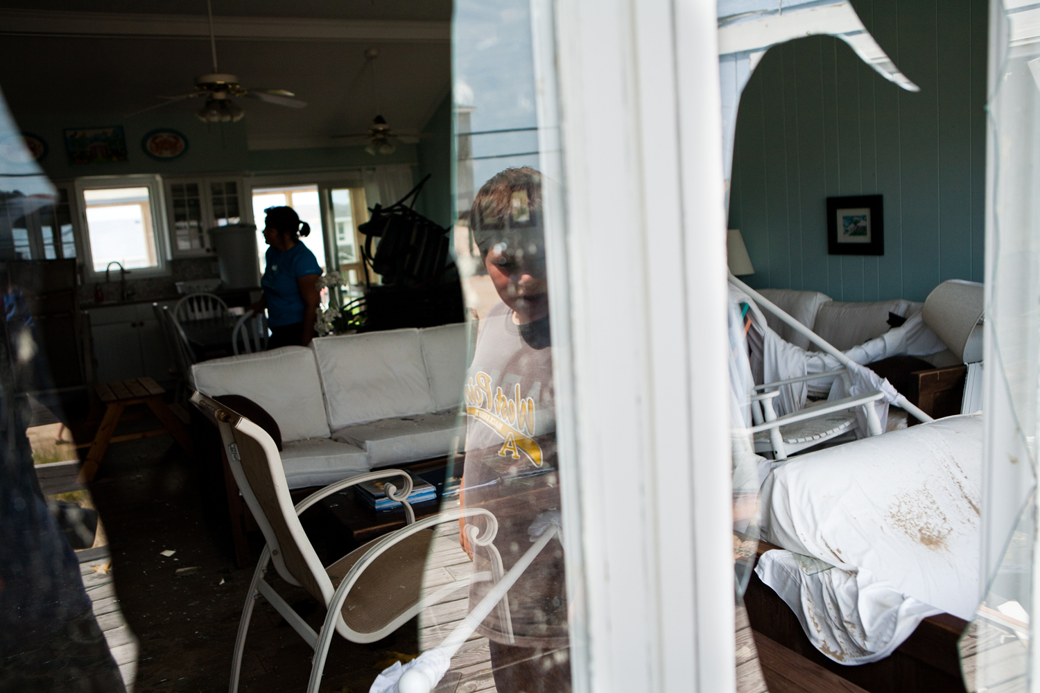 August 28, 2011, Virginia Beach, VA. Michael Black, 10, is reflected in a broken window of his family's vacation house in Sandbridge the day after a tornado spawned by Hurricane Irene passed through the town.