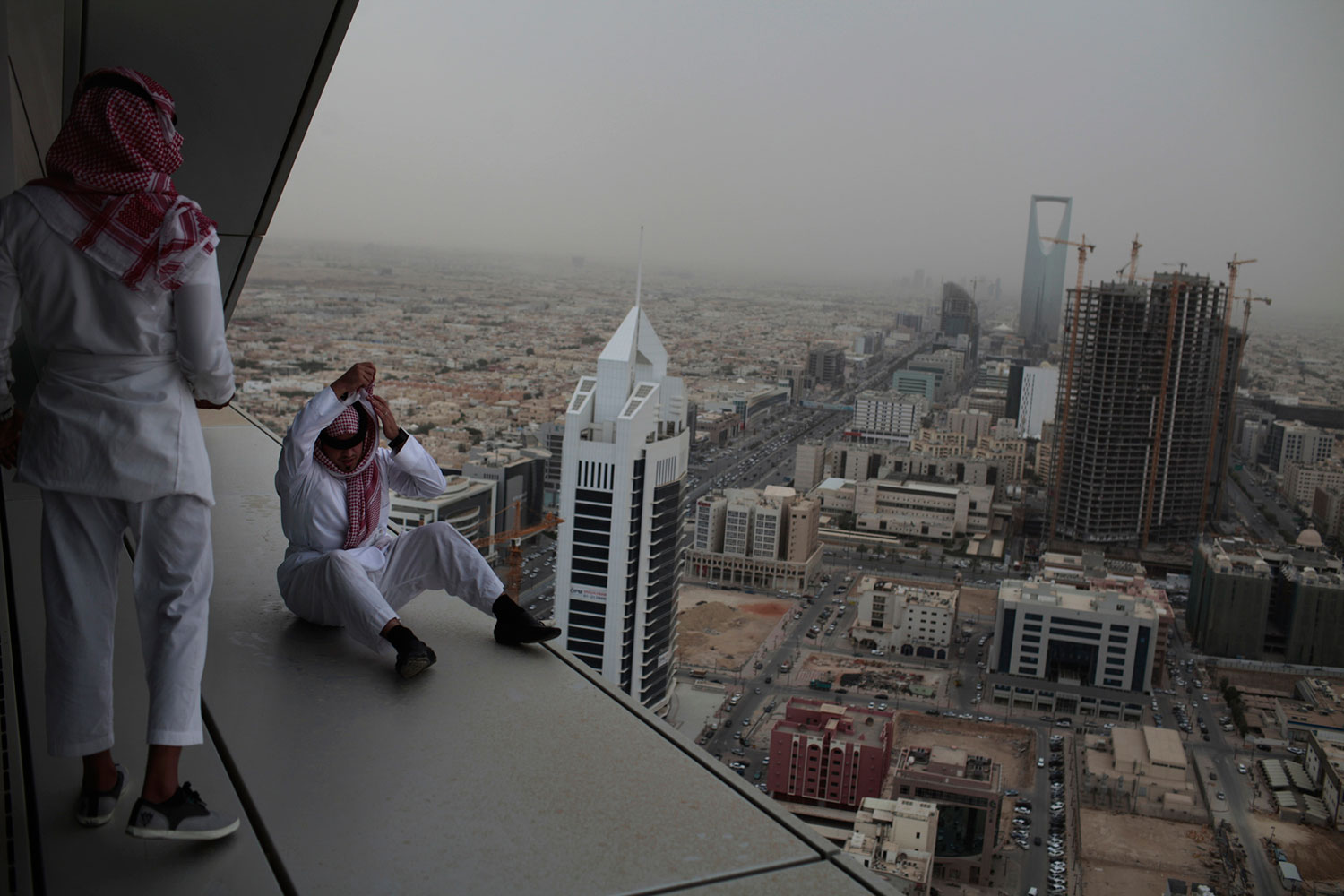 Riyadh, Saudi Arabia. May 23, 2011.                                Upper class Saudi youth dare each other inch closer and closer to the ledge of a high-rise building in Riyadh. In country with a high standard of living but very few options for entertainment (cinemas and clubs are banned), Saudi youth resort to the most random things to entertain themselves.