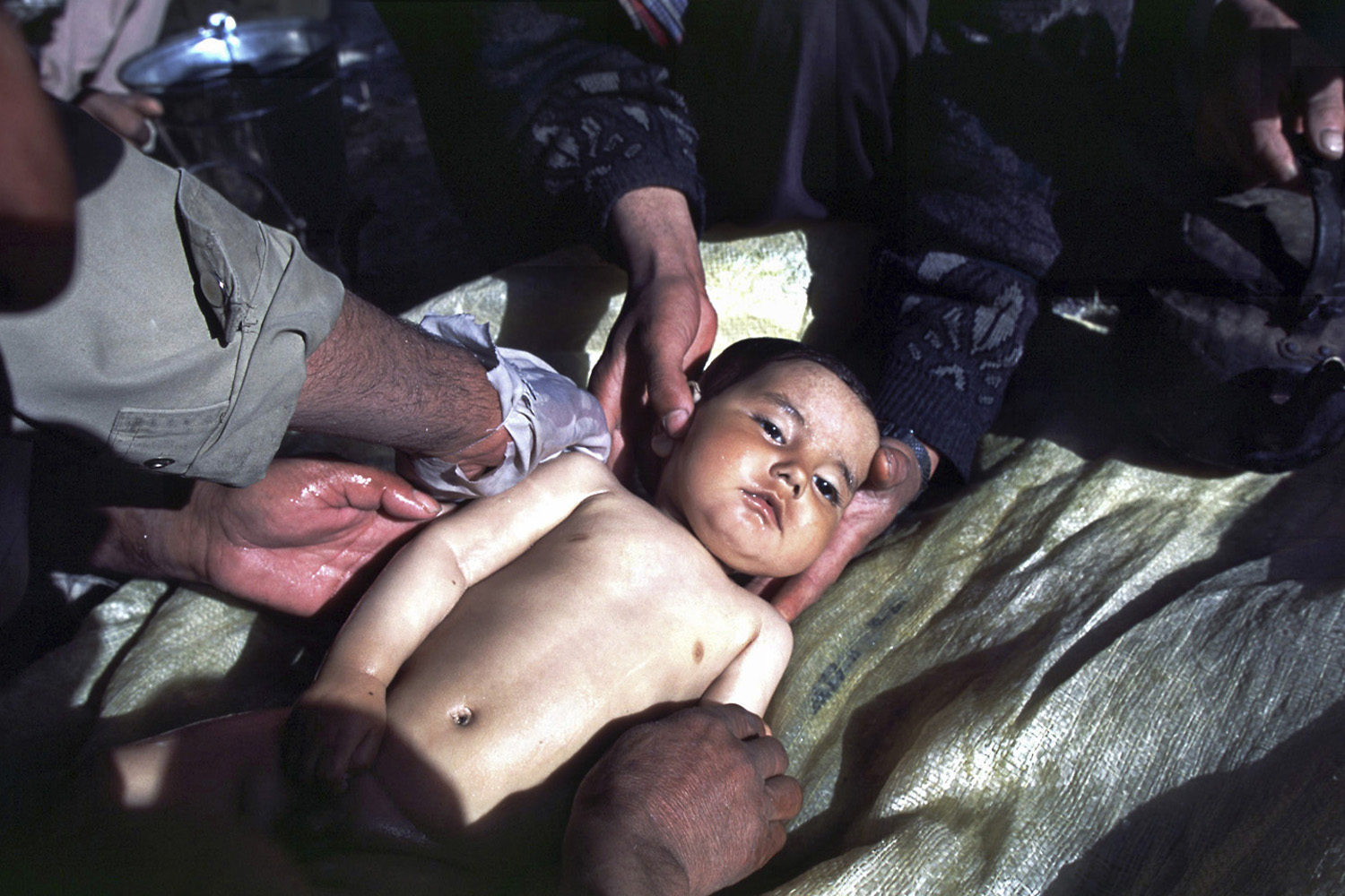 Men wash the body of a dead one-year-old, Abdullah, before a traditional Islamic burial. The baby died from exposure because the Taliban refused to allow UN aid and supplies to be delivered to internally displaced refugees. February, 2001