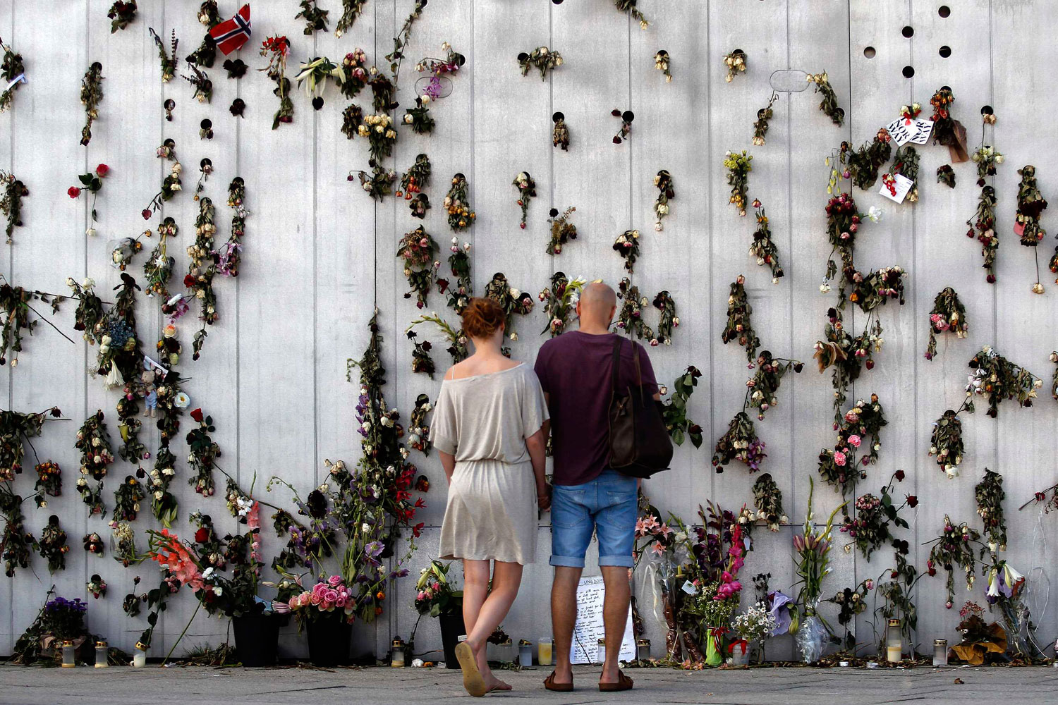 July 29, 2011. A couple stands in front of a wall decorated with flowers in memory of the victims of the previous week's attacks, in Oslo. Norwegians united in mourning as the first funerals were held a week after anti-Islam zealot Anders Behring Breivik massacred 77 people in attacks that traumatized the nation.