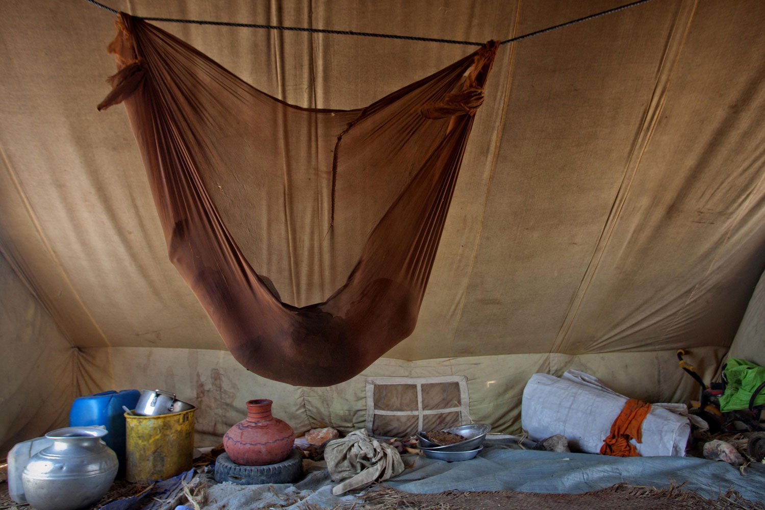 July 31, 2011. One and a half-year-old Muskan, internally displaced by the 2010 floods, sleeps in a hammock over cooking utensils inside her family's tent set up along a roadside in Jamshoro, in Sindh province. More than 800,000 flood affected families remain without permanent shelter, according to the aid group Oxfam, and more than a million people need food assistance.